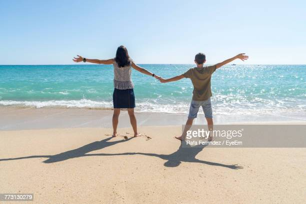 Rear View Of Mother And Son With Arms Outstretched Standing At Beach Against Clear Sky