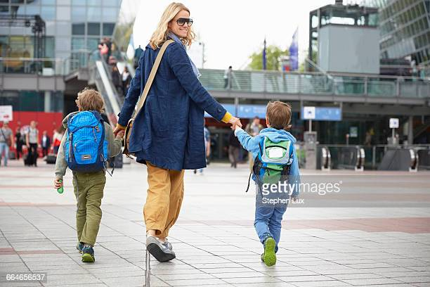 Rear view of mother and sons at airport holding hands