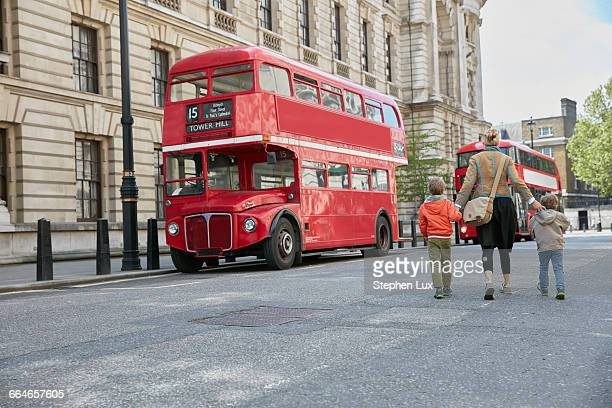 rear view of mother and sons looking at red double decker bus - double decker bus stock pictures, royalty-free photos & images