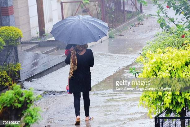 Rear View Of Mother Carrying Child And Umbrella During Monsoon