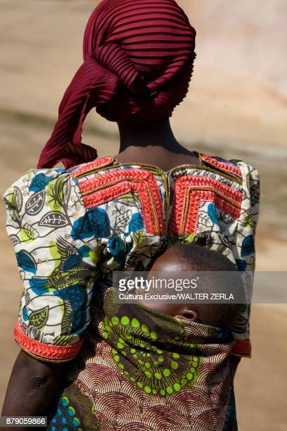 Rear view of mother carrying child in baby sling, Masango, Cibitoke, Burundi, Africa