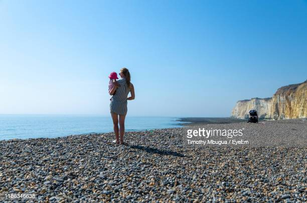 rear view of mother carrying daughter while looking at sea against clear sky - clear sky stock pictures, royalty-free photos & images