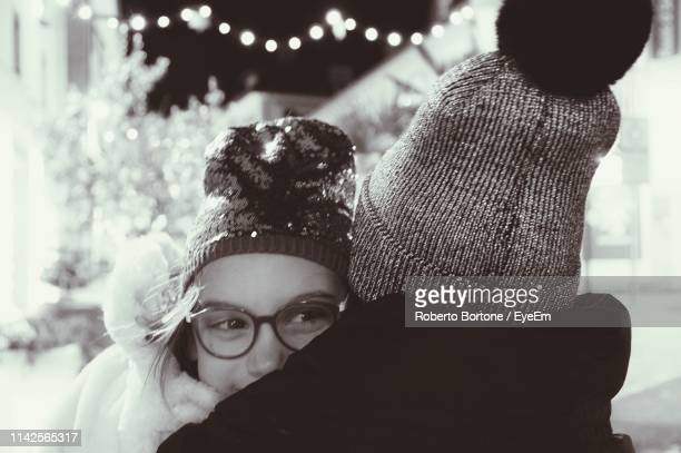 Rear View Of Mother Carrying Daughter While Standing Outdoors During Winter At Night