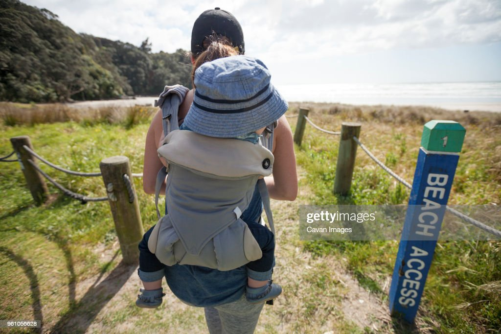 Rear View Of Mother Carrying Son In Baby Carrier While Walking At