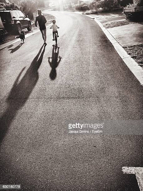 Rear View Of Mother Jogging By Boy Riding Bicycle On Road