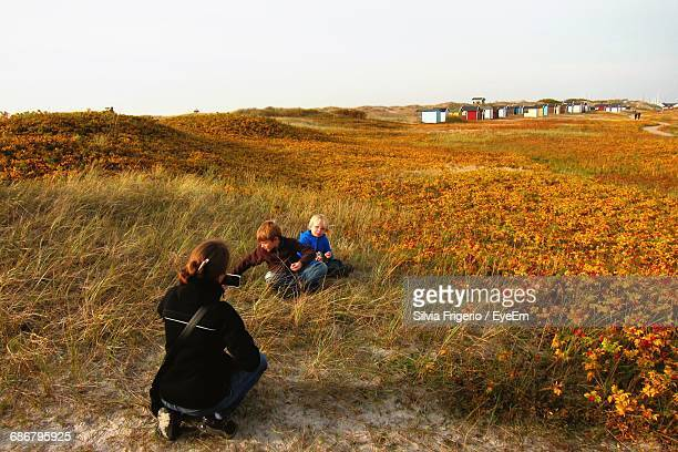 Rear View Of Mother Photographing Children On Field Against Clear Sky