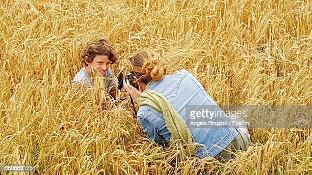 Rear View Of Mother Photographing Son In Field Using Camera