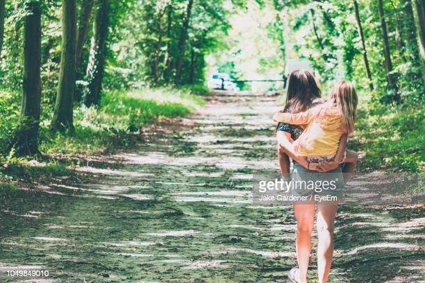 rear view of mother piggybacking daughter while walking in forest - oise stock pictures, royalty-free photos & images