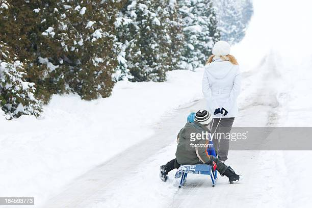Rear View OF Mother Pulling Her Sons On Sled