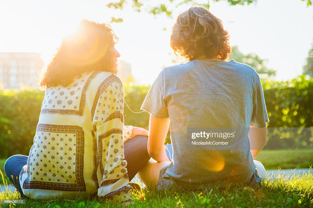 Rear view of mother sharing music sitting with teenager son : Stock Photo