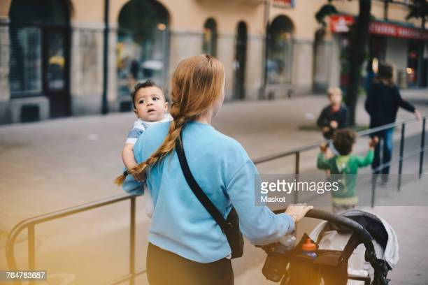 rear view of mother walking with sons while pushing baby stroller on sidewalk in city - cochecito para niños fotografías e imágenes de stock
