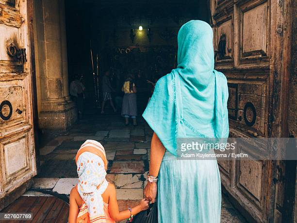 rear view of mother with child entering church of holy sepulchre - israeli woman stock pictures, royalty-free photos & images