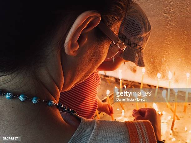 Rear View Of Mother With Child Lighting Candles In Church