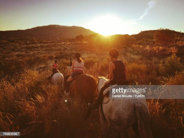 rear view of mother with children horseback riding on field during sunset - andare a cavallo foto e immagini stock