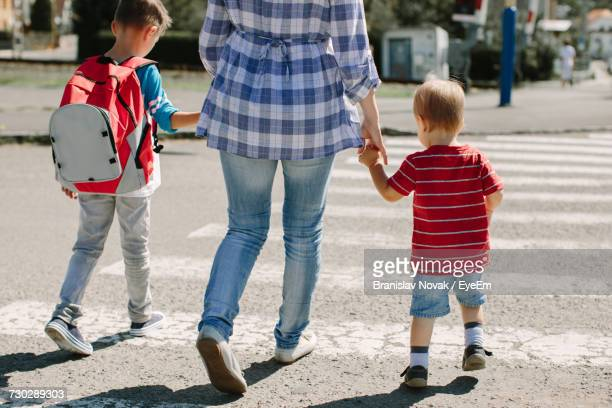 rear view of mother with children - family with two children stock photos and pictures