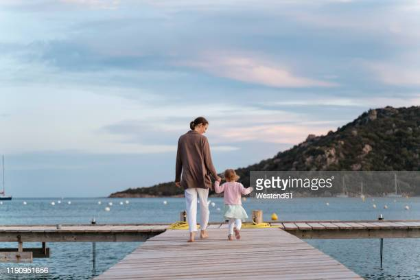 rear view of mother with daughter walking on a jetty at sunset - jetty stock pictures, royalty-free photos & images