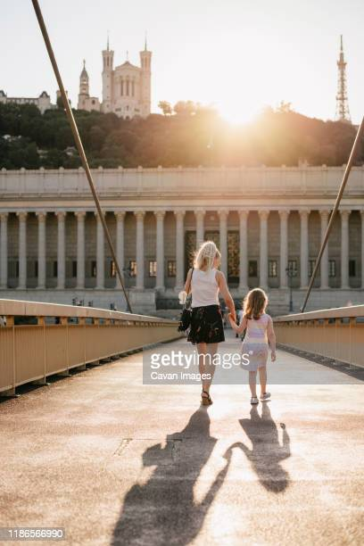 rear view of mother with daughter walking on palais-de-justice footbridge against sky during sunset - twilight stock pictures, royalty-free photos & images
