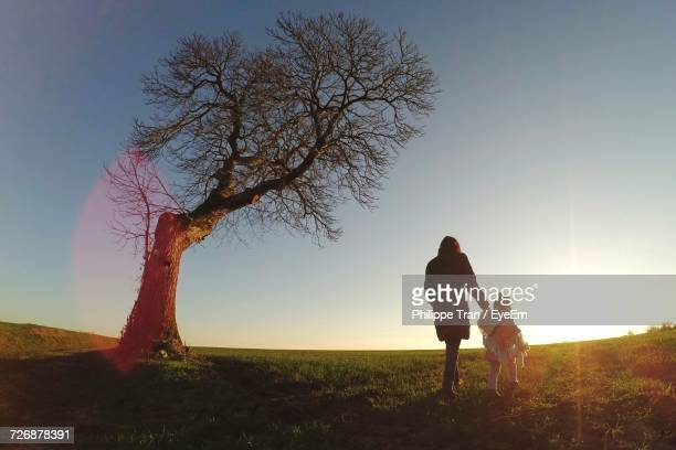 Rear View Of Mother With Little Daughter Walking By Bare Tree On Grassy Field Against Sky