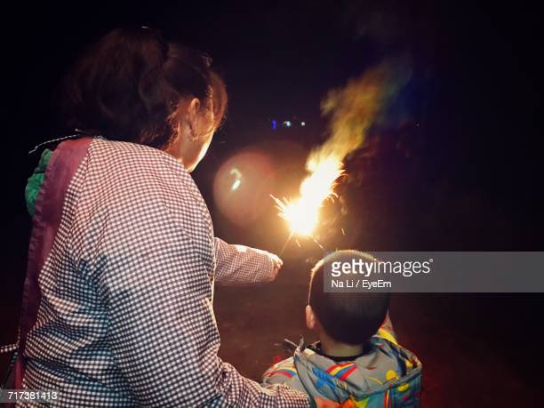 Rear View Of Mother With Son Burning Sparklers At Night