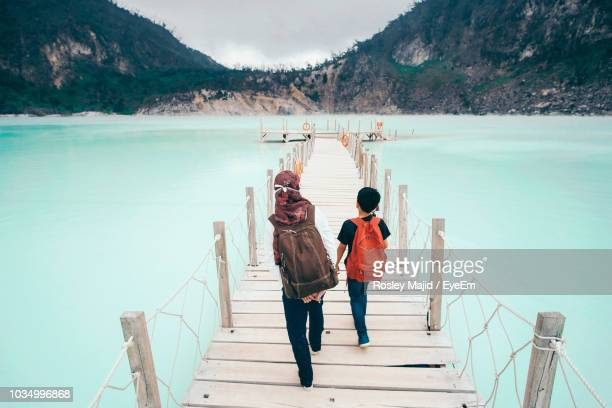 rear view of mother with son walking on pier over lake - bandung stock pictures, royalty-free photos & images