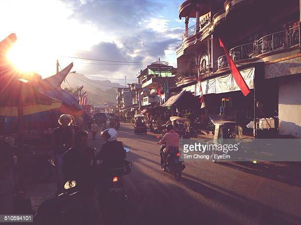 rear view of motorbikes on street along built structures - rantepao stock photos and pictures