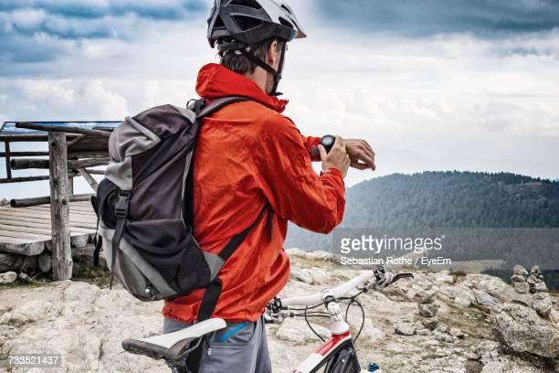 Rear View Of Mountain Biker Looking At Smart Watch Against Cloudy Sky