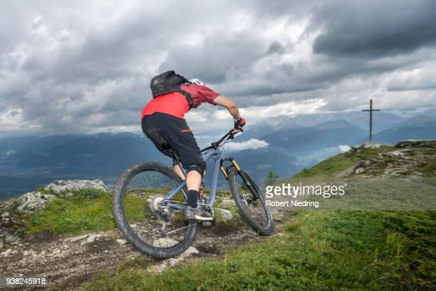 Rear view of mountain biker riding on uphill, Trentino-Alto Adige, Italy