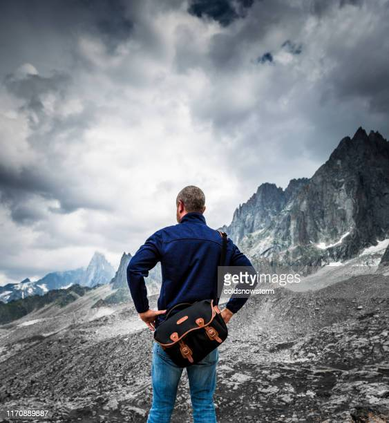 rear view of mountain man enjoying freedom in nature - shoulder bag stock pictures, royalty-free photos & images