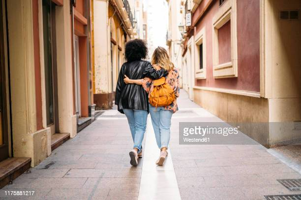 rear view of multicultural women walking in the city, almeria, spain - arm in arm stock pictures, royalty-free photos & images