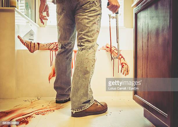 rear view of murderer holding hacksaw with woman lying in bathtub at home - murdered women stock pictures, royalty-free photos & images