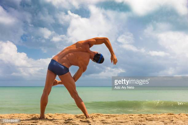 rear view of muscular male swimmer on beach bending over sideways - man bending over from behind stock photos and pictures