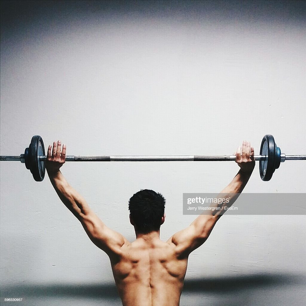 Rear View Of Muscular Man Lifted Barbell Against Wall : Stock Photo
