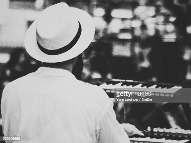 Rear View Of Musician Playing Piano At Music Concert
