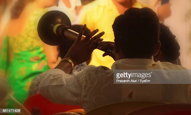 rear view of musician playing shehnai at wedding ceremony - indian music stock photos and pictures