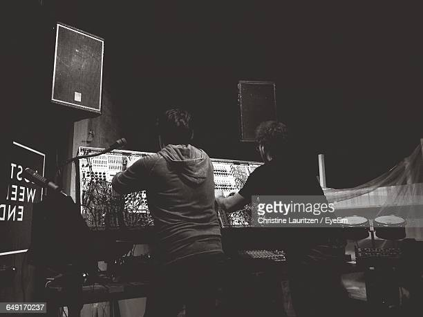 rear view of musician playing synthesizer at music concert - electronic music stock pictures, royalty-free photos & images
