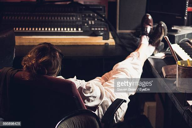 Rear View Of Musician Relaxing On Chair At Studio