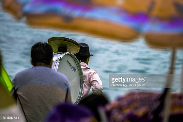 Rear View Of Musicians Carrying Drum At Beach
