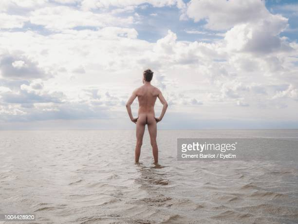 rear view of naked man standing with arms akimbo in sea against sky - hombres desnudos fotografías e imágenes de stock