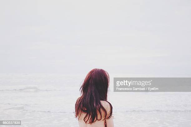 Rear View Of Naked Woman At Beach Against Sea