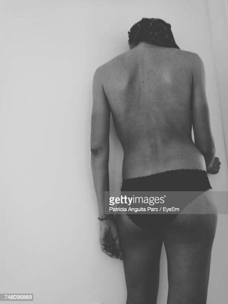 Rear View Of Naked Woman In Underwear Standing Against Wall