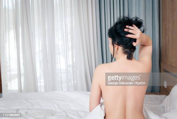 rear view of naked woman posing on bed at home - oben ohne frau stock-fotos und bilder