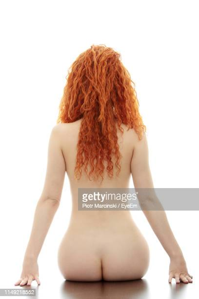 rear view of naked woman sitting against white background - beautiful bare bottoms stock pictures, royalty-free photos & images