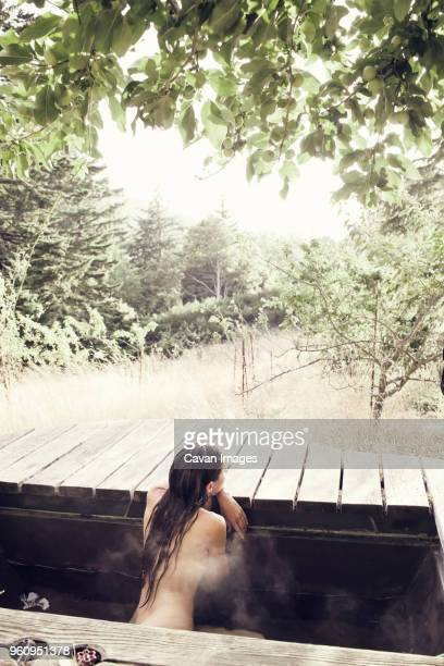 Rear view of naked woman sitting in hot spring