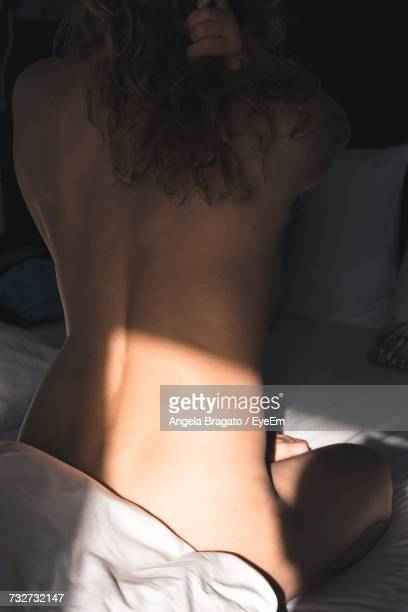 Rear View Of Naked Woman Sitting On Bed