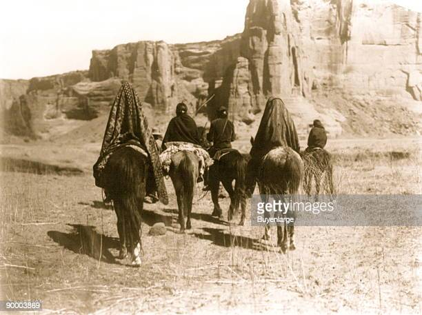 Rear view of Navajo Indians on horseback making their way over the sparse dry grassy floor of Tesacod Canyon