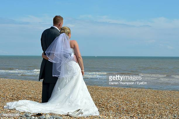 rear view of newlywed on beach against sky - religious occupation stock pictures, royalty-free photos & images