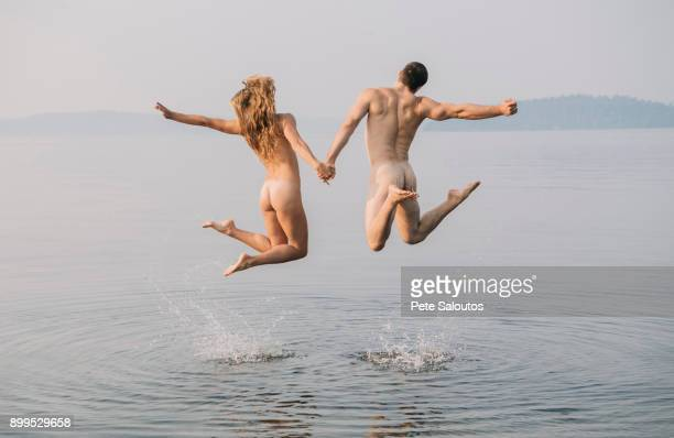 Rear view of nude couple in water jumping in mid air
