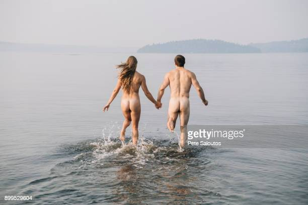 Rear view of nude couple running into water