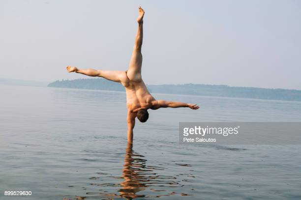 Rear view of nude man doing handstand in water