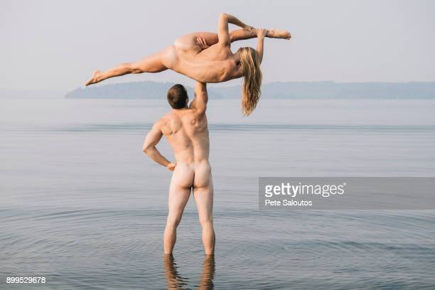 rear view of nude man lifting nude woman doing the splits - male female nude stock pictures, royalty-free photos & images